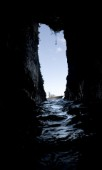 View of a boat floating in the water, through the narrow opening of a dark cave in Costa Rica.
