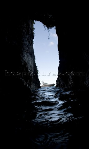 View of a boat floating in the water through the narrow opening of a dark cave in Costa Rica