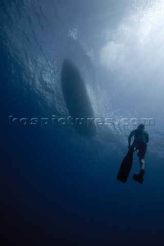 A view of a free diver underwater as he returns to the boat floating above in Costa Rica