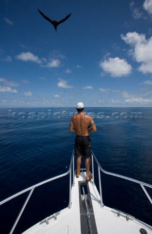 A man fishing off bow of boat as a bird flies through the clouds overhead in the waters off of Costa