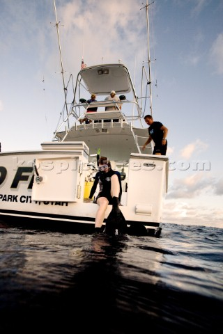A woman wearing goggles snorkel and flippers sits on the edge of a boats dive door preparing for a d