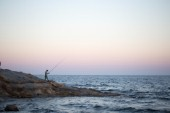 A man fishing at sunset in Calpe, Alicante.