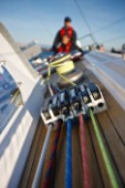A  closeup shot of lines and line stoppers on the deck of  the Swan 48 sloop, COLIBRI, with Sean Broe (upper) and Anton Muzik (lower) in the background, sailing on the waters of San Francisco Bay on October 21, 2008.