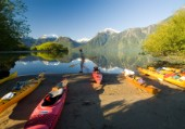 Ben Sanders walks past a group of kayaks while holding a paddle in Lago Yelcho, Chile.