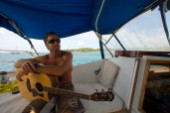 Captain Brian Carson takes a break from sailing the Nene to entertain his guests with a few songs, Hanalei Bay, Na Pali Coast, Kauai, Hawaii