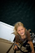 Young girl (6-7 years) climbing the rigging of a sailboat, Maine.