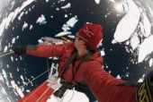 Man shoots a picture of himself as he climbs the mast of a ship in Antarctica and looks down from a great height.