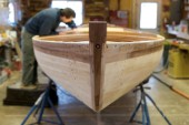 Boat builder, Alec Brainard works on the boat he is restoring at his business Artisan Boatworks in Rockport, Maine.