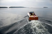 Power boat Gemma heads for home on calm seas. Islands dot the horizon and lobster buoys are sprinkled across the water on a gray day  in Penobscot Bay, Maine, USA  Model and Property Release:RP07011_Gemma_JamesBrady  RM07007_JamesBrady