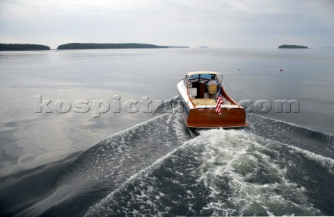 Power boat Gemma heads for home on calm seas Islands dot the horizon and lobster buoys are sprinkled