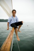 Man smiling on bowsprit of sailboat, Casco Bay, Maine, New England. (releasecode: rausher and rausherPR)
