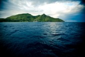 A white boat sailing on the dark blue waters of the Flores Sea sails buy one of the lush tropical islands of the Nusa Tenggara region near Flores, Indonesia just prior to a storm approaching.