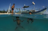 Filipino boys swim from off an outrigger boat anchored on shore. Boracay Philippines.