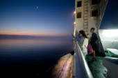 On the deck of a trans-Adriatic car ferry crossing an adventurous travelers watches the sunrise over calm seas.