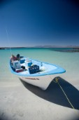 Blue and white mexican fishing boat is mored on the sand beach of the sea of cortez near Loreto, Mexico.