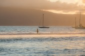 A solo surfer rides a long slow wave with sailboats and an island in the distance off the coast of Maui.
