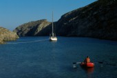 Small red rubber boat and sail boat. Joanna B. Pinneo/Aurora Photos/Kos Pictures