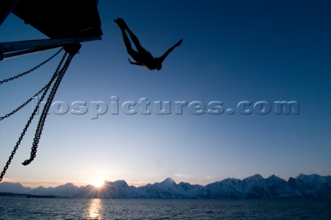 A man dives from a boat into the  Lyngen Fjord in northern Norways Lyngen Alps Kari MedigAurora Phot
