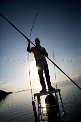 A flats boat captain poles through shallow water in the Everglades while silhouetted by the sun at d