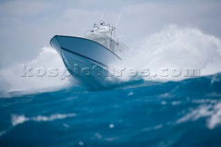 A white powerboat speeds through blue water while crashing through the waves. Chris Ross/Aurora Photos/Kos Pictures