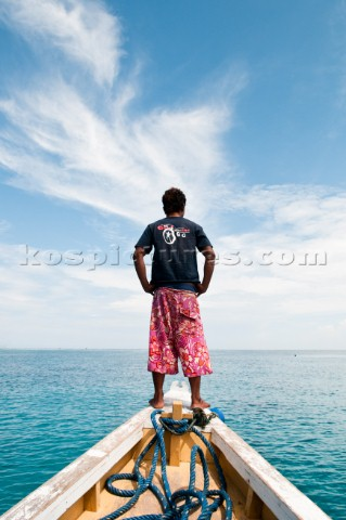 Rear view of an Indonesian man standing on a boat bow scanning the ocean near Gili Air Gili Island L