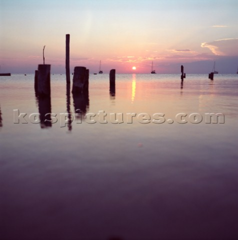 The sun sets behind sail boats as seen from the island of Caye Caulker Belize Karl SchatzAurora Phot