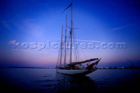 A classic yacht rests at anchor in the calm evening hours Casco Bay Portland Maine Peter DennenAuror
