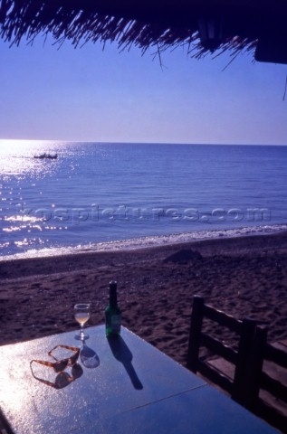 Greece Lesvos Glass of wine on a beachfront table Skala Eressos Steve OutramAurora PhotosKos Picture