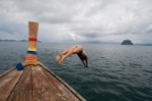Female in bikini takes a plunge off of a longtail boat in Thailand.