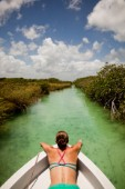 A young woman in a bikini sits in the bow of a white boat as it moves through teal-green water of the Sian Kaan Preserve. David Hanson/Aurora Photos/Kos Pictures