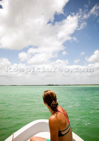 A young woman in a bikini sits in the bow of a white boat as it moves through tealgreen water of the